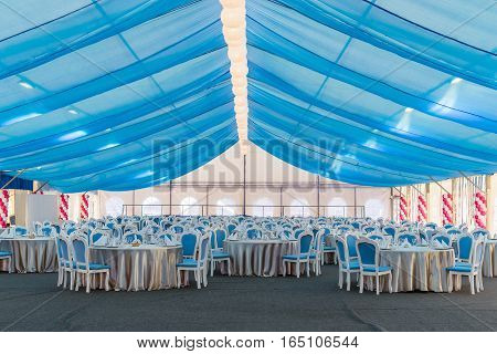 An empty banquet hall. Big tent with blue curtains tables and chairs for a large number of guests. holiday decoration dinner party.