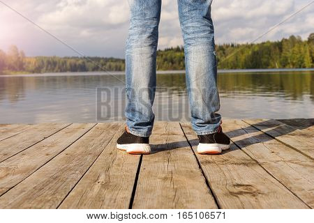 Springboard into the water Unity with nature concept. A man stands at the edge of the pier. Legs men. Freedom and peace. Landscape. Early autumn. Rainy clouds.