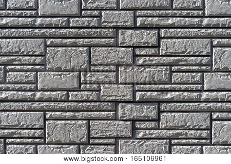 Wall from a decorative stone. Texture architectural background tiles of various sizes. Artificial stone
