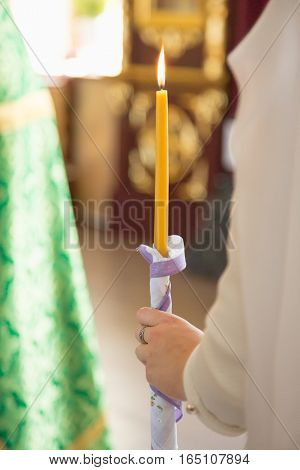 white candles in the hands of the bride and groom in church.