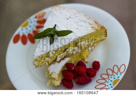 Cake, sponge cake with strawberry and green mint sprinkled with powdered