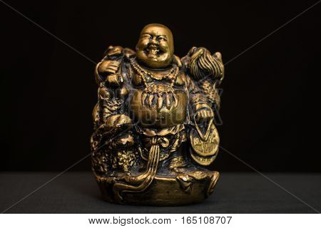 Chinese figurine Hotei, the laughing Buddha is a symbol of prosperity and money, unfocused
