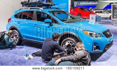 DETROIT MI/USA - JANUARY 12 2017: Three engineers reverse-engineering (competitive analysis) a car at the North American International Auto Show (NAIAS).