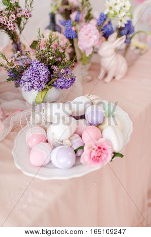 Easter still life - vase with flowers, decorative eggs on a plate and rabbit