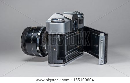 Old film camera photographed on a light background. The camera photographed from behind with an open back cover.