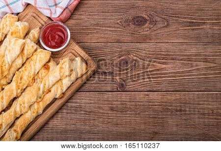 Puff pastry cheese twistson the wooden table.