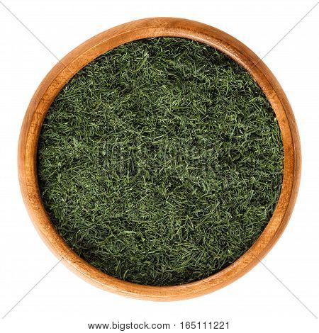 Dried dill fronds in wooden bowl, also called dill weed. Shredded green leaves of Anethum graveolens, used as herb and spice. Isolated macro food photo close up from above on white background.