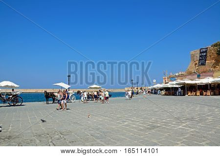 CHANIA, CRETE - SEPTEMBER 16, 2016 - Tourists walking along the quayside with restaurants and San Nicolo bastion to the rear and horse drawn carriages to the right hand side Chania Crete Greece Europe, September 16, 2016.