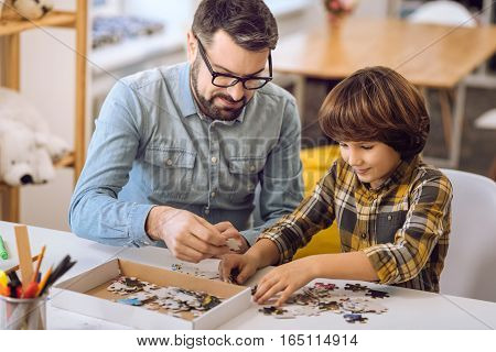 it would be surprise. Serious bearded man wearing glasses holding puzzle thinking where to put it
