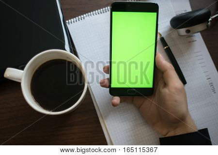 Laptop and headphones smartphone with green screen for key chroma screen.  On the table with notebook and pen.