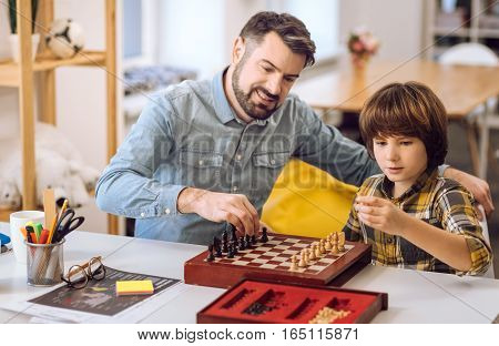 It is your move. Serious boy wearing checked shirt holding pawn in his left hand while looking at it