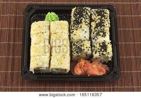 Sushi rolls in black plastic container on brown wicker straw mat closeup