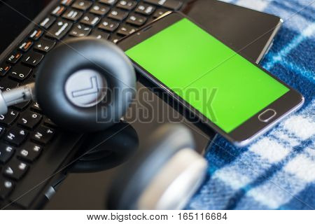 Laptop and headphones smartphone with green screen for key chroma screen. In vintage blue bedspread