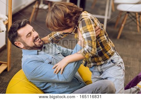 Feeling happiness. Positive delighted male wearing jeans and shirt looking at his little son while sitting on poufs