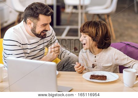 For strength. Happy attractive bearded man wearing stripped sweater looking at his son while feeding him
