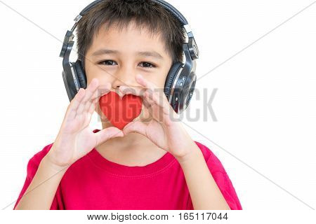 A boy wearing headphones and wearing a red shirt holding a red heart concept for valentines day.