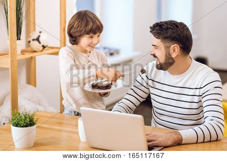 Good day. Attractive youngster wearing beige sweater standing near the table while giving a piece of cake to his dad