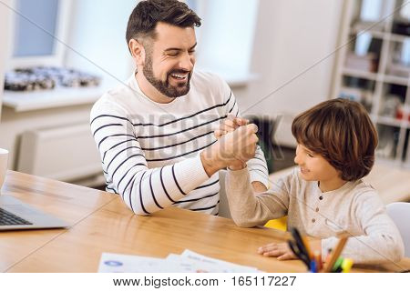 Just do it. Handsome little boy looking sideways sitting near his father while competing on arms