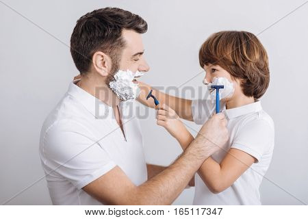Try it. Handsome young father and his son with shaving foam on their faces are looking each other standing in semi position over white background