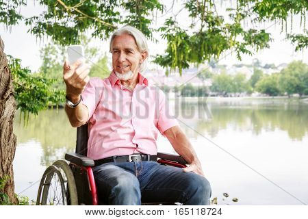 Senior man in wheelchair, taking a selfie with his phone.