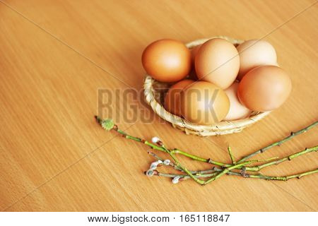 The eggs in a small wicker basket. Next to the basket on wooden surface lie several blossoming willow twigs. All the objects - symbols of the holidays Easter and palm Sunday.