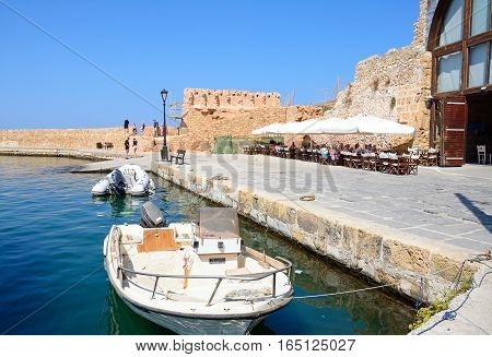CHANIA, CRETE - SEPTEMBER 16, 2016 - Small boats moored along the quayside with a restaurant and harbour wall to the rear Chania Crete Greece Europe, September 16, 2016.