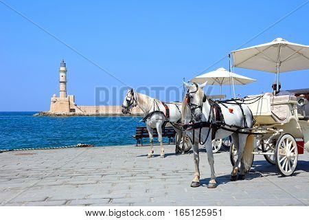 CHANIA, CRETE - SEPTEMBER 16, 2016 - Horse drawn carriages on the quayside with the Venetian lighthouse at the harbour entrance to the rear Chania Crete Greece Europe, September 16, 2016.
