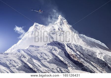 Rescue helicopter over snowy mountain peak. Nepal, Manaslu