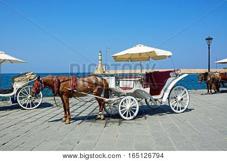 Horse drawn carriages on the quayside with the Venetian lighthouse at the harbour entrance to the rear Chania Crete Greece Europe.