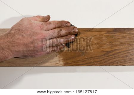 Male hand rubbing oil paint into piece of wood. Handicraft. Making furniture concept