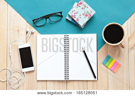 Still life, business, office supplies or education concept : Top view of working desk with blank notebook with pencil, coffee cup, colorful note pad, eyeglasses and mobile phone on wooden background