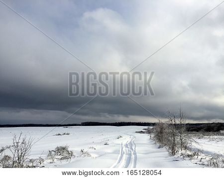 Road littered with snow in the field, outdoor horizontal shot