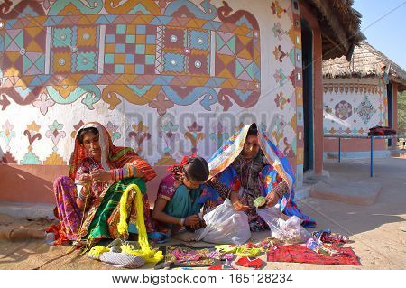 GUJARAT, INDIA - DECEMBER 20, 2013: Tribal women in front of their house (Bhunga) in a local village near Bhuj