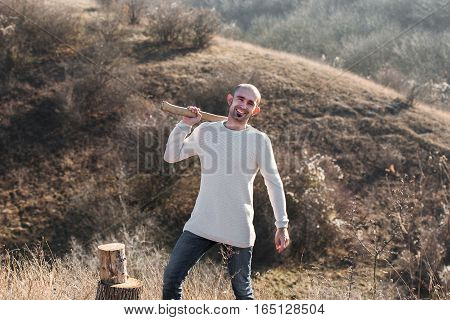 Man in jeans and sweater chopping wood with ax