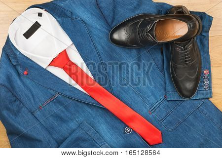 Denim jacket and red tie and classic black shoes men's fashion. View from above