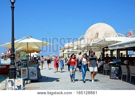 CHANIA, CRETE - SEPTEMBER 16, 2016 - Tourists walking along the quayside with the Turkish mosque to the rear Chania Crete Greece Europe, September 16, 2016.