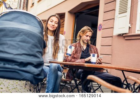 Young parents with baby stroller having coffee at a cafe in Heidelberg, Germany.