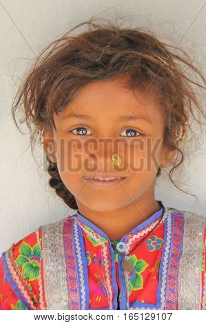 HODKA, GUJARAT, INDIA - DECEMBER 20, 2013: Portrait of a cute and colorful little girl in Hodka, local village near Bhuj