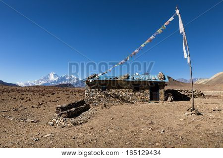 stone house with colored flags on a background of mountains Himalayas Nepal.