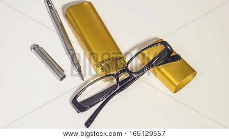 Black glasses, gold case and pen on the isolate white background