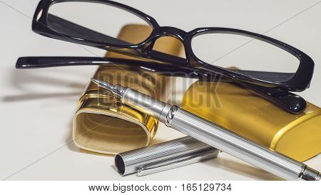 The glasses, gold case and a pen. White isolate background. Closeup.