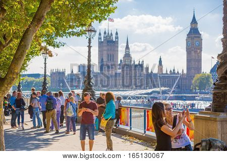 LONDON, UK - SEPTEMBER 10, 2015: Embankment of River Thames with lots walking people. Big Ben and Houses of Parliament at the background