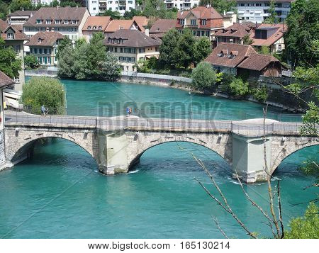 Stone bridge over clean alpine Aare river with clean water and swiss historical houses on bank in city of BERN BERNE in SWITZERLAND at warm sunny summer day, EUROPE on JULY