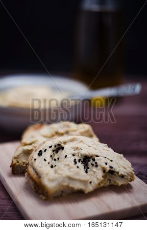 Sandwiches with hummus on the wooden board.