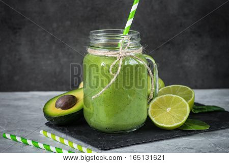 Healthy green smoothie in mason jar and ingredients. Superfoods detox diet healthy food. Lime apple spinach avocado and lime