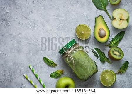 Healthy green smoothie in mason jar and ingredients. Superfoods detox diet healthy food. Lime apple spinach avocado and lime. Green food background
