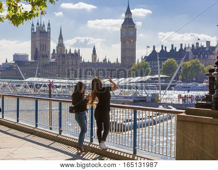 LONDON, UK - SEPTEMBER 10, 2015: Young girls making photos against of Big Ben and Houses of Parliament. View from the River Thames embankment