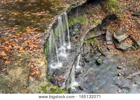 Water plunges from tiered ledges with autumn foliage all around at Oglebay Falls a waterfall in Wheeling West Virginia.