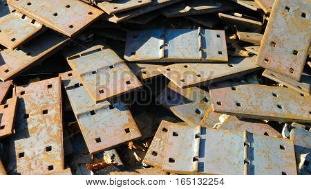 Old rusty steel plates from railroad strewn in a pile
