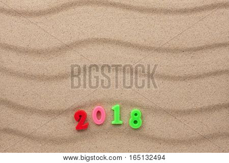 New year 2018 written in the sand with space for your text
